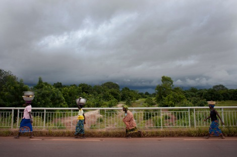Women walk along a highway as storm clouds gather outside Sikasso