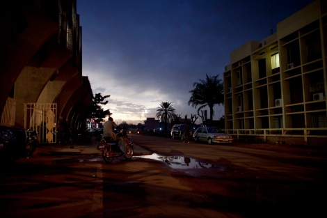 A man drives his motorcycle down a street at dusk in downtown Ouagadougou