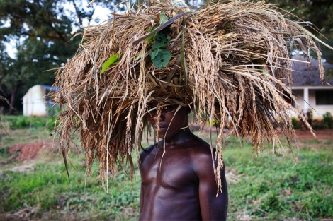 A farmers with wheat on his head poses for a picture as he walks home after a day's work in Guiledge