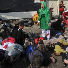 """12-year-old Tarana Akbari cries out near dead and injured people after a suicide bomber killed more than 70 civilians during a religious ceremony at the Abul Fazel shrine in the center of Kabul, where Shia Muslims were marking the Day of Ashura, on December 6, 2011. Agence France-Presse photographer Massoud Hossaini won the agency's first Pulitzer Prize for the picture on April 16, 2012 in the breaking news photography category """"for his heartbreaking image of a girl crying in fear after a suicide bomber's attack at a crowded shrine in Kabul."""" (Massoud Hossaini/AFP/Getty Images)"""