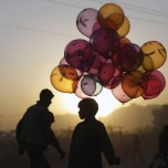 Mahfouz Bahbah, 12, stands on a roadside hoping to sell his balloons during sunset in Kabul, on October 18, 2011. (AP Photo/Muhammed Muheisen)