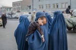 A young boy sleeps on a woman's shoulder in the Old City on November 7, 2012 in Kabul. (Daniel Berehulak/Getty Images)