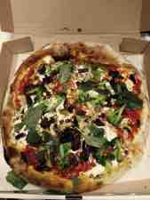Pizza with mushroom, broccoli, olives; woodfired and topped with fresh basil.
