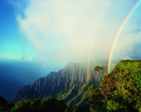 A double rainbow arcs above the jagged cliffs and dense vegetation of Kalalau, the largest valley on Na Pali in Hawaii. By Diane Cook.