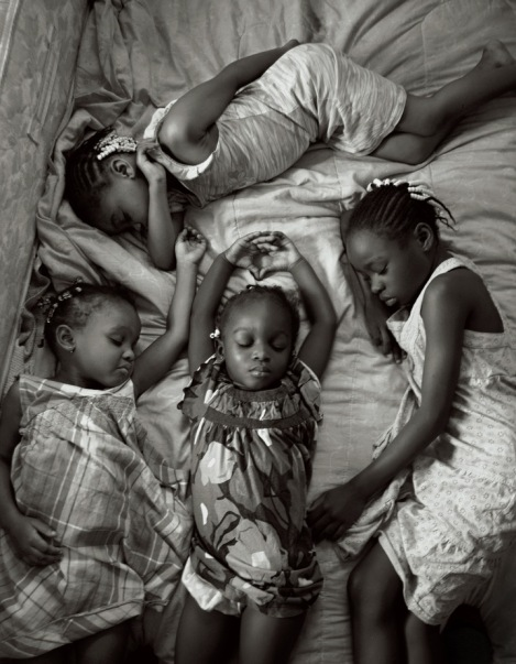 Nestled in their bed in Miami, four young sisters nap on a Sunday afternoon after attending church. By Maggie Steber.