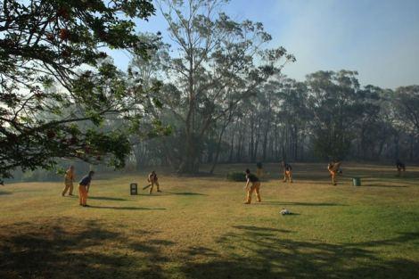 Warrimoo firefighters relax by playing a game of cricket near Norman Lindsay House in Faulconbridge, New South Wales, Australia. (By John Donegan/ABC Australia).