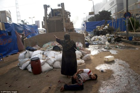 An Egyptian woman in Cairo tries to stop a bulldozer from hurting a wounded youth. There is debate if this is a military or state security bulldozer, but either way, it reminded many of that famous photo in Tiananmen Square in China. For me it sums up a city destroyed, civilians wounded, and the able-bodied doing whatever they could to help those they could. (By AFP/Getty)