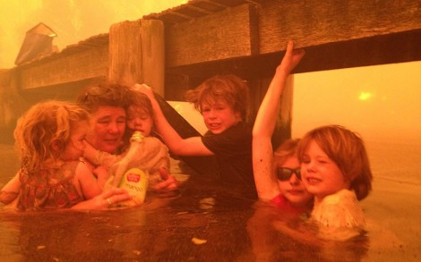 The Holmes family -- grandparents and five grandchildren -- who waded into the sea near Dunally, Tasmania, to shelter from the fire under a jetty. This photo was taken so send to the children's mother so she knew they were ok (By Tim Holmes)