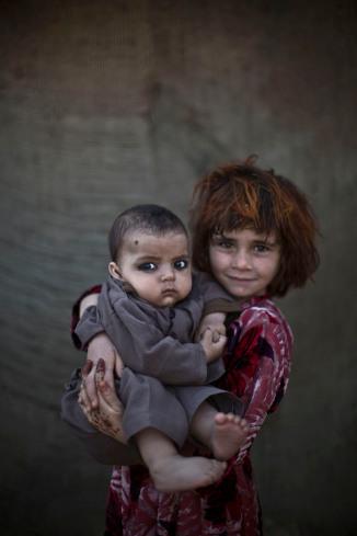 Khalzarin Zirgul, 6, holds her cousin, Zaman, 3 months.