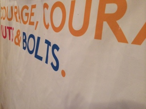 Foyer banner: 'Courage, courage, nuts and bolts'