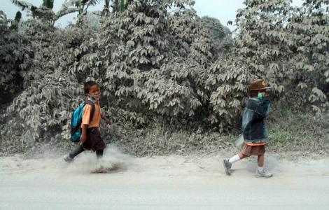 Indonesian students walk on street covered in Mt. Sinabung volcanic ash; Sukandebi village, Indonesia (EPA)