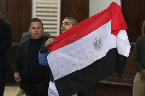 Mohamed Fahmy, a Canadian journalist of Al-Jazeera English, holds up an Egyptian flag after a retrial at a courthouse near Tora prison in Cairo, Egypt, Thursday, Feb. 12, 2015. An Egyptian judge ordered Fahmy and another Al-Jazeera English journalist, Baher Mohammed, released on bail Thursday as their retrial on terror-related charges continues. Associated Press (12 February 2015)