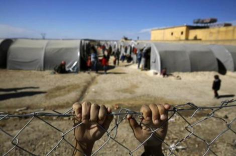 Kurdish boy, who fled violence in Kobani, grasps fence that surrounds a refugee camp, Suruc (Reuters) #Syria