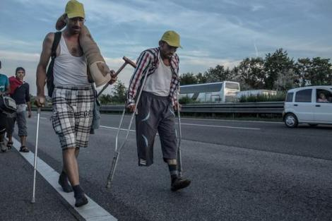 Two friends from Aleppo, Syria, walk 170km from Budapest to Austria to reach safety. One in socks and carrying his friends prosthetic leg. The other (who I understand lost his leg in the Syrian war) on crutches. (Photo: @DanielEtterFoto)