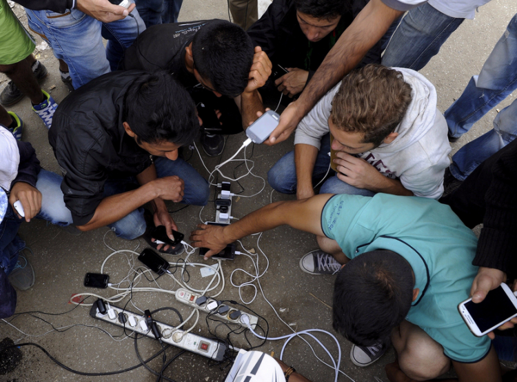 Refugees and migrants charge their mobile phones as they wait to cross the borders of Greece with Macedonia (Alexandros Avramidis/Reuters)