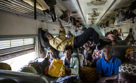 A man stretching across the second-class compartment (Photo: Glenna Gordon)