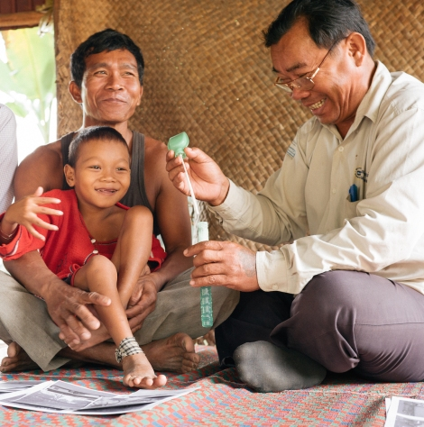 Seven-year-old Mai sits in his father's lap as he blows bubbles with his disability worker Somalai. Blowing bubbles helps children with a communication and swallowing disability improve their muscle control, which helps them speak more clearly. (Photo: Hugo Sharp/OIC: The Cambodia Project)