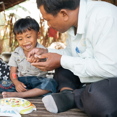 Four-year-old Makara shows a wide smile as he plays a game with Sokha, his disability worker. Makara has a communication disability, and Sokha is helping him overcome it. (Photo: Hugo Sharp/OIC: The Cambodia Project)