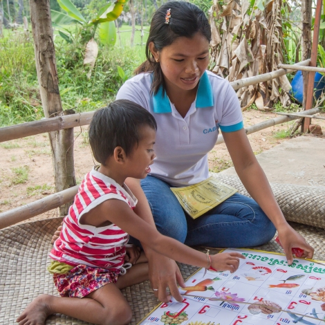 Disability worker Chhean helps Tai say the alphabet as part of Tai's therapy to help her overcome her communication disability. (Photo: Anna Betts/OIC: The Cambodia Project)