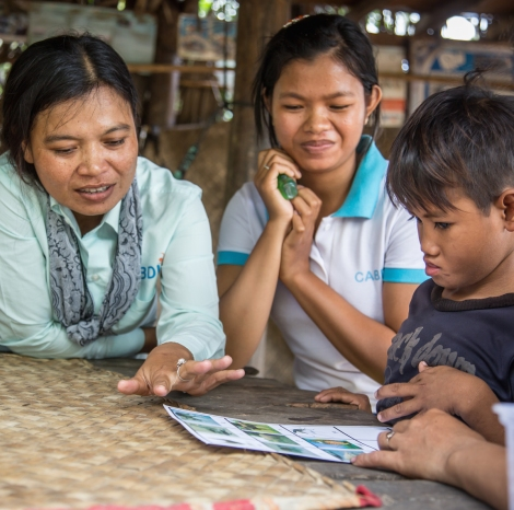 Socheat names animals as his disability workers Disability workers Phearom and Chhean look on. Socheat has a communication disability, and this is just one exercise to help him improve his communication. (Photo: Anna Betts/OIC: The Cambodia Project)