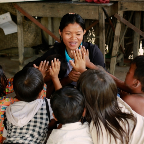 Disability worker Chhean high-fives children in the home of a child who receives speech therapy (Photo: Mona Simon/OIC: The Cambodia Project)