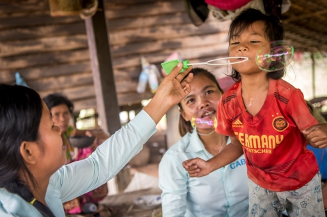 Disability workers playing speech therapy games with six-year old Tai. (Photo: Anna Betts/OIC: The Cambodia Project)