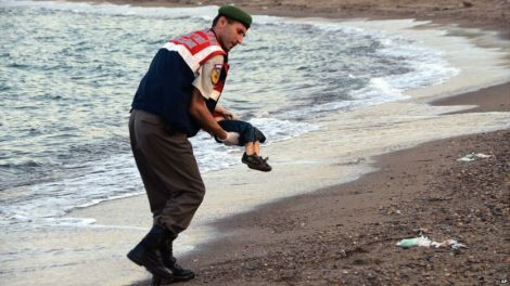 A Turkish police officer carries Alan Kurdi, who drowned in a failed attempt to sail from Turkey to the Greek island of Kos (Nilufer Demir)