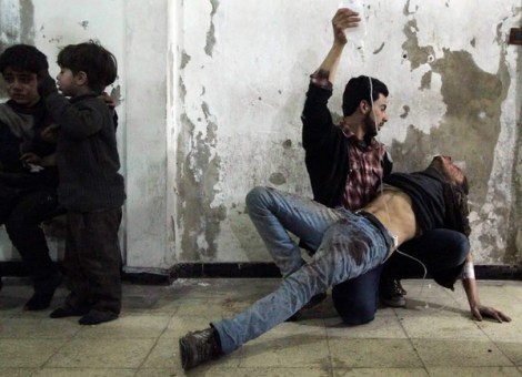 Man helps injured man after reported airstrike by forces of Syria's Pres Assad; Damascus. (Reuters)