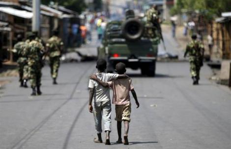 Boys walk behind patrolling soldiers in Bujumbura, Burundi (Goran Tomasevic/Reuters)