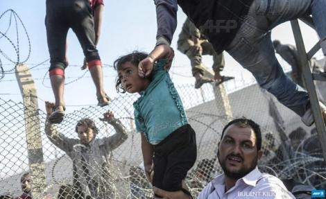 Young girl is lifted as #Syrian's rush through border fences to enter Turkish territory (@Kilicbil #AFP)