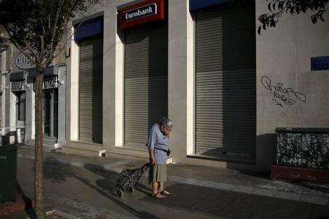 A woman pulling a shopping cart reacts outside a closed Eurobank branch in Athens, Greece (Reuters)