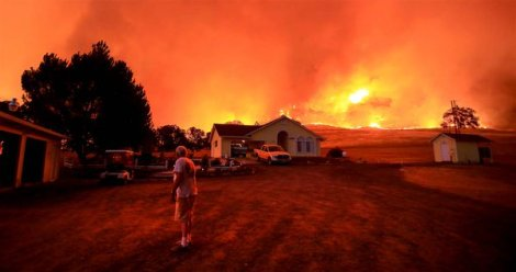 Wall of flames lurches over ridge as a resident of Morgan Valley Road, California, prepares to evacuate (AP)
