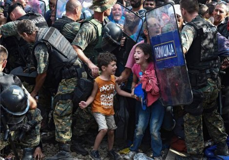 Children cry as refugees waiting on Greek side of border break through Macedonian police into Macedonia (EPA)
