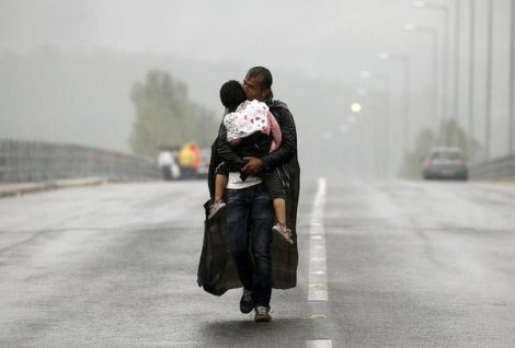 Syrian refugee kisses his son as he walks towards Greece's border with Macedonia (@yannisBehrakis /Reuters)