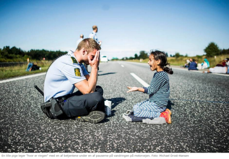 Refugee girl plays 'Where's the ring' with Danish police officer; hwy btwn Den-Swe (Michael Drost-Hansen)