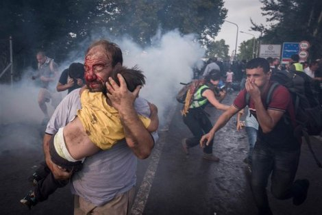 Refugee holds child during clash with Hungarian riot police at border crossing in Serbia (@SergeyPonomarev)