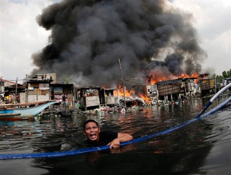 A man escapes from a fire in Paranaque city, south of Manila, Philippines (Francis R. Malasig/EPA)