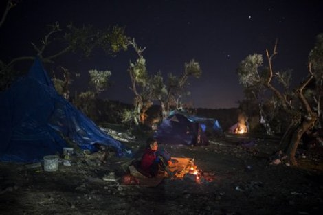 Afghan refugee boy tries to warm up next to bonfire at night in Moria village on Greek island of Lesbos(AP)