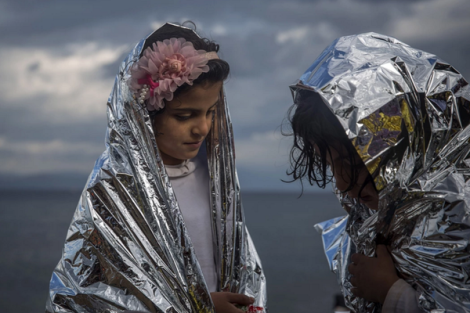 Two refugee girls wear thermal blankets given by volunteers after arrival on Lesbos (@SantiPalacios /AP)